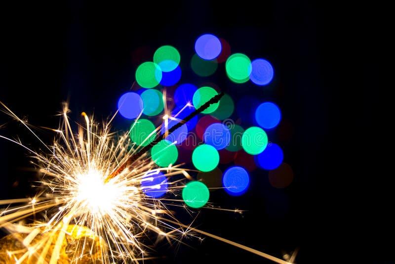 Fuoco del Bengala su un fondo nero e su una struttura blu vaga del nuovo anno delle luci del bokeh fotografie stock libere da diritti