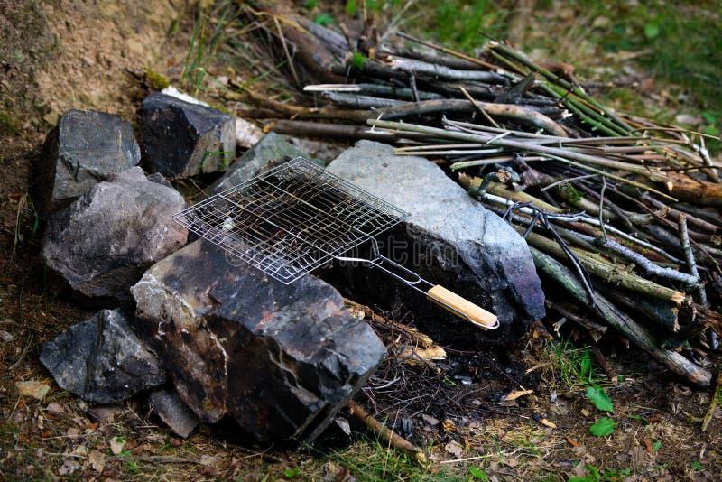 Fuoco di accampamento con il canestro grigliante vuoto, alimento di campeggio di stile di vita di avventura fotografie stock libere da diritti