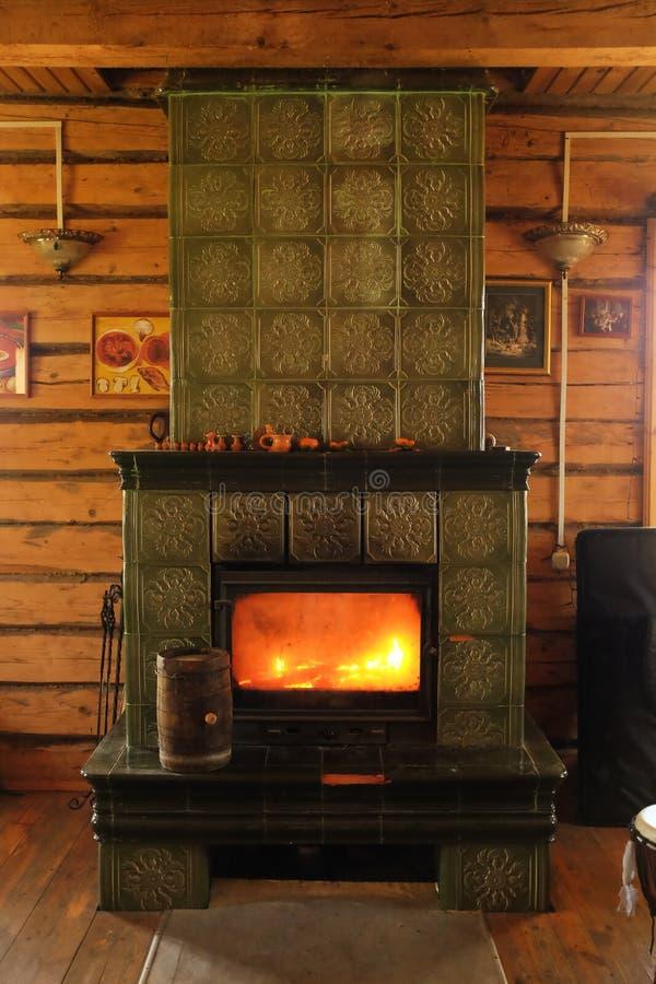 Fuoco di urlo dentro la stufa bruciante di legno nel vecchio villaggio di legno della casa, casa d'annata immagini stock libere da diritti