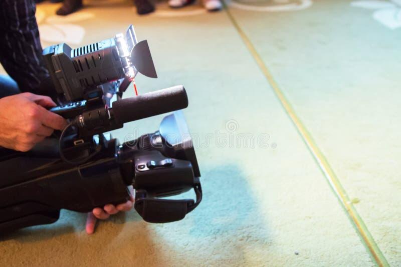 Fuoco e confuso morbidi dell'operatore professionista e del cineoperatore della videocamera che lavora con la sua attrezzatura pr fotografia stock