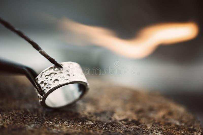 Fuoco e ghiaccio Vista del primo piano di bello anello d'argento sul banco da lavoro del gioielliere pronto per saldare immagine stock libera da diritti