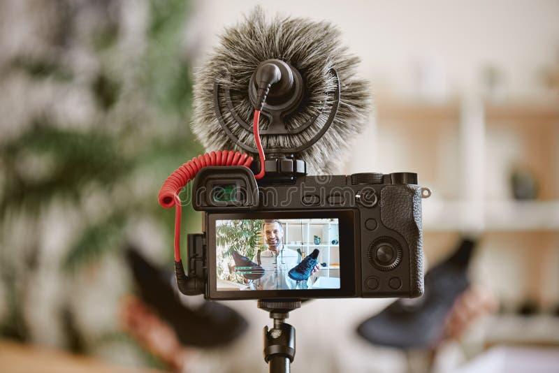 A fuoco Foto alta vicina dell'esposizione della macchina fotografica con il blogger maschio allegro che tiene le scarpe da tennis immagine stock libera da diritti