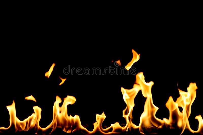 Fuoco giallo con le linguette della fiamma isolate sul nero fotografia stock libera da diritti