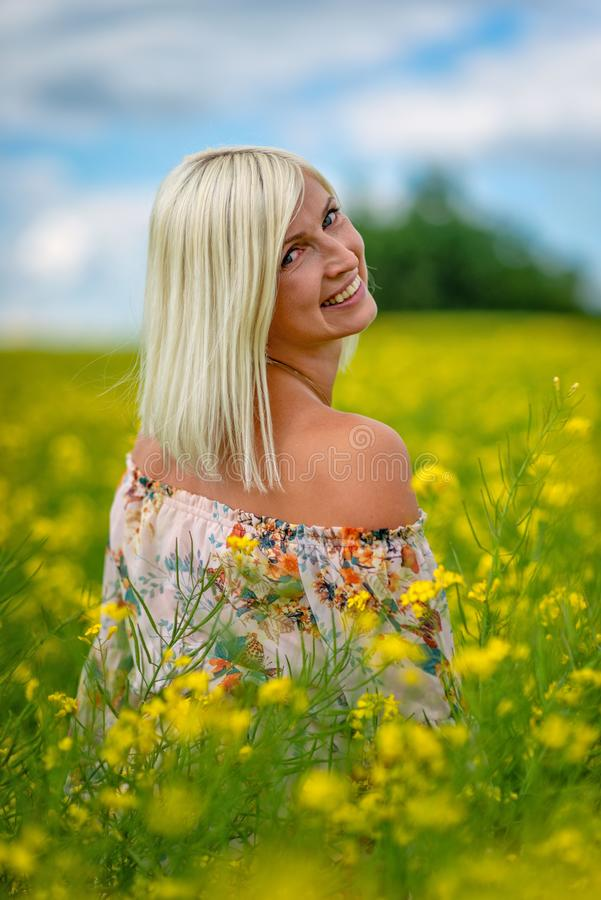 Fuoco molle e selettivo Bella, donna attraente e bionda in un prato giallo del fiore fotografia stock libera da diritti