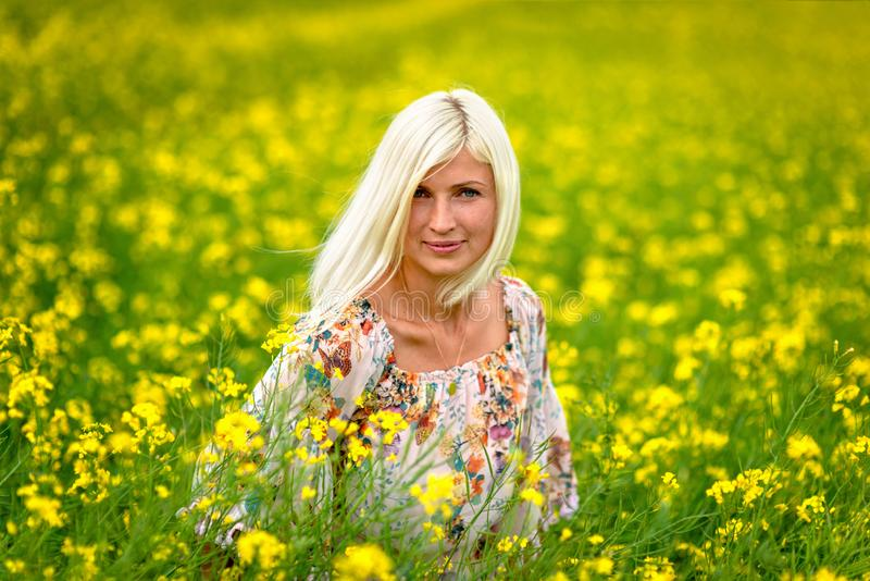Fuoco molle e selettivo Bella, donna attraente e bionda in un prato giallo del fiore immagini stock