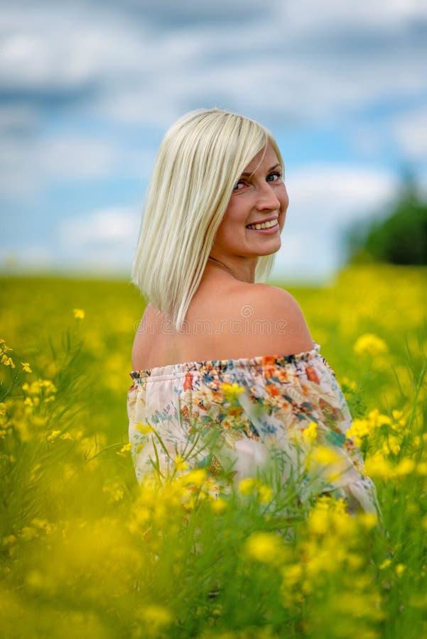 Fuoco molle e selettivo Bella, donna attraente e bionda in un prato giallo del fiore immagine stock libera da diritti