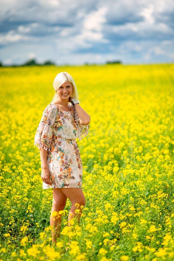 Fuoco molle e selettivo Bella, donna attraente e bionda in un prato giallo del fiore fotografia stock