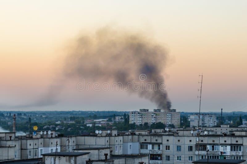 Fuoco nella città in un grattacielo, fumo nero sopra le case nella sera immagini stock libere da diritti