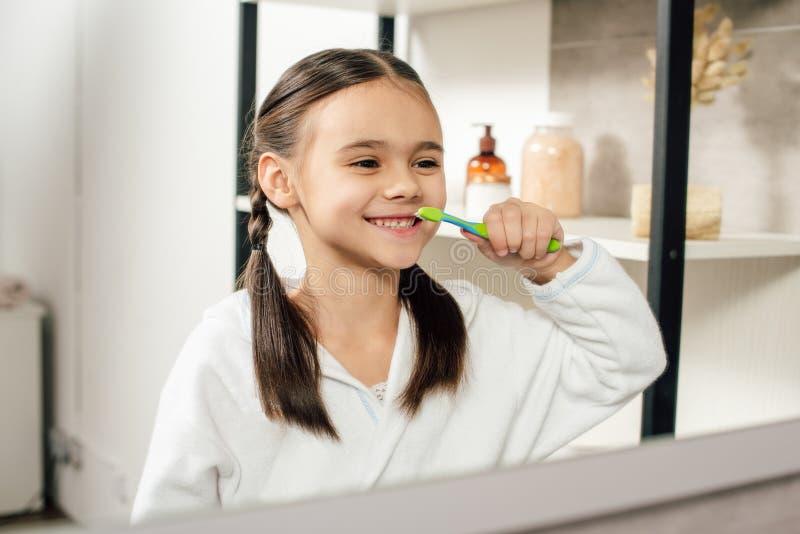 fuoco selettivo del bambino in accappatoio bianco che guardano per rispecchiarsi e denti di spazzolatura fotografia stock libera da diritti