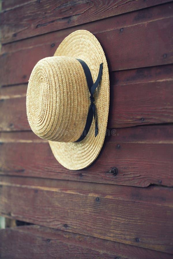 Fuoco selettivo del cappello di paglia dell'uomo di Amish sulla porta di granaio fotografia stock