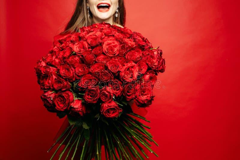 Fuoco selettivo del mazzo delle rose rosse in mani della donna immagini stock libere da diritti