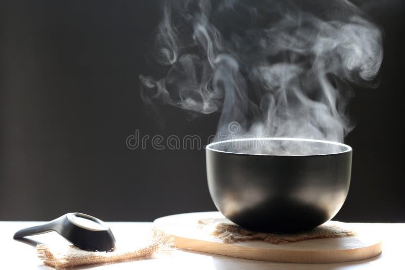 Fuoco selettivo dell'aumento del fumo con la minestra calda in tazza e cucchiaio o fotografie stock libere da diritti