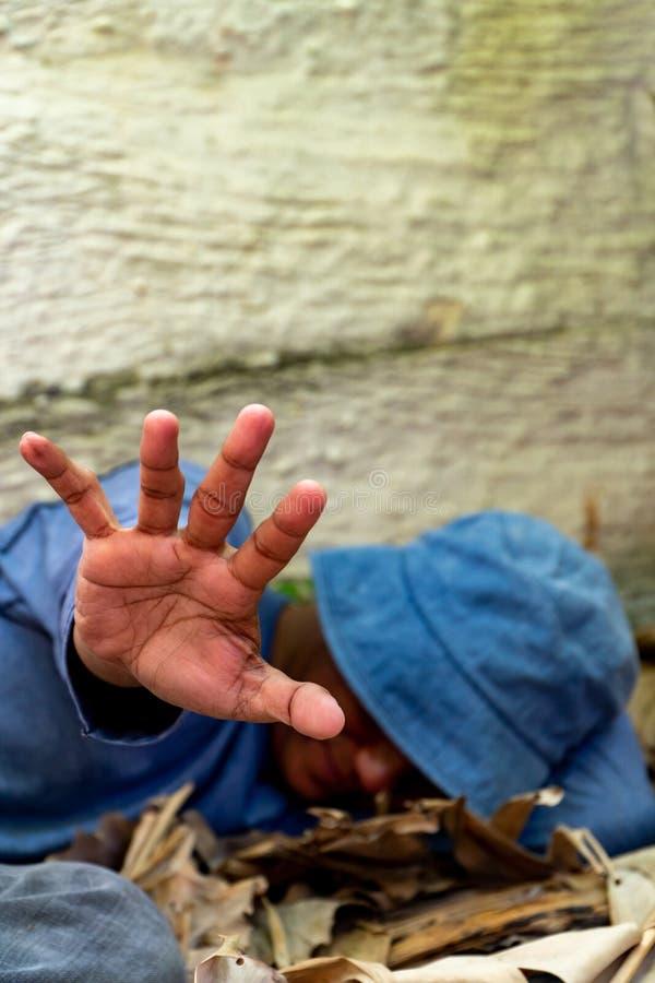 Fuoco selettivo della mano sporca senza tetto in casa abbandonata Lui che ha provato a sollevare la sua mano per impedire il peri fotografia stock libera da diritti