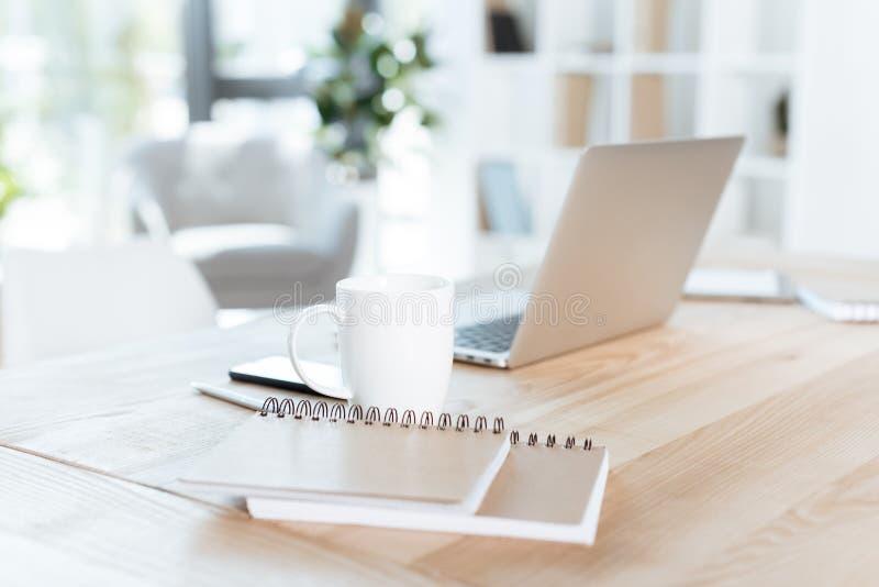 fuoco selettivo della tazza e del computer portatile di caffè nel luogo di lavoro fotografia stock