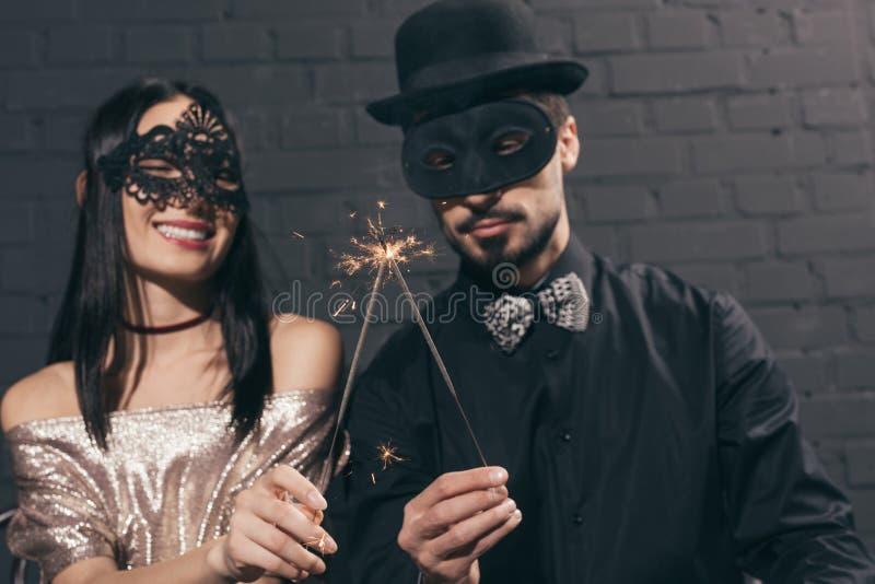 fuoco selettivo delle coppie multietniche alla moda nelle maschere di natale con le scintille a nuovo immagini stock