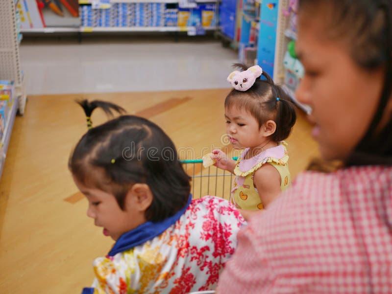 Fuoco selettivo di poca neonata asiatica il più ulteriormente che guarda e che sta in un carrello con sua sorella immagini stock libere da diritti