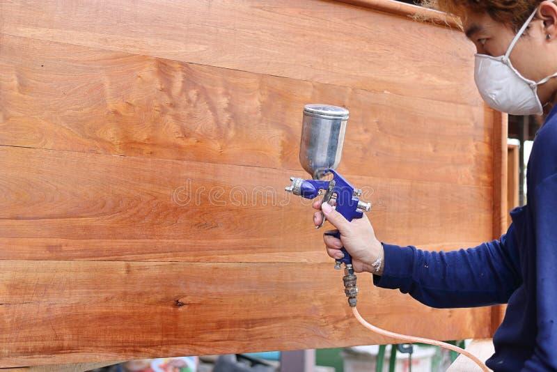 Fuoco selettivo sulle mani del pittore industriale con la maschera di sicurezza che dipinge una mobilia di legno con la pistola a immagine stock libera da diritti