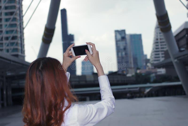Fuoco selettivo sulle mani di giovane donna asiatica attraente che prende una foto al fondo urbano della città fotografia stock libera da diritti