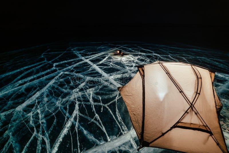 Fuoco su ghiaccio alla notte Campeggio su ghiaccio La tenda sta accanto al falò Lago Baikal Vicino c'è automobile Tenda di riparo fotografie stock libere da diritti