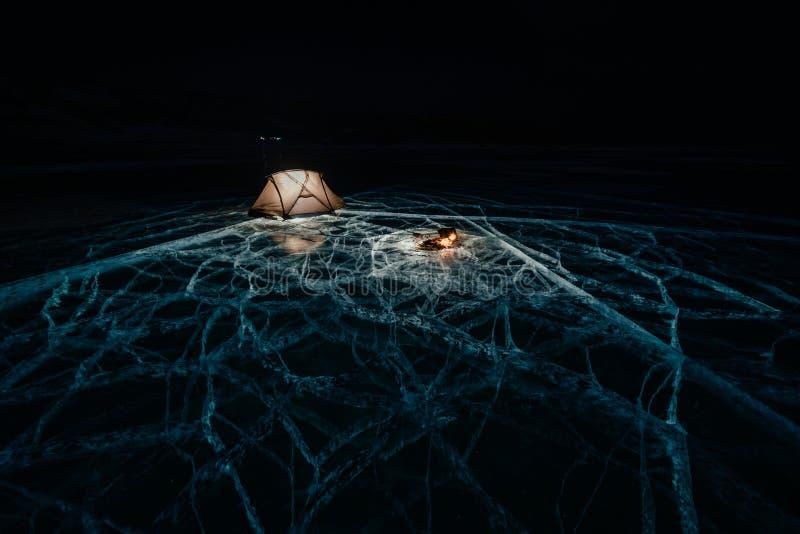 Fuoco su ghiaccio alla notte Campeggio su ghiaccio La tenda sta accanto al falò Lago Baikal Vicino c'è automobile Tenda di riparo immagine stock libera da diritti