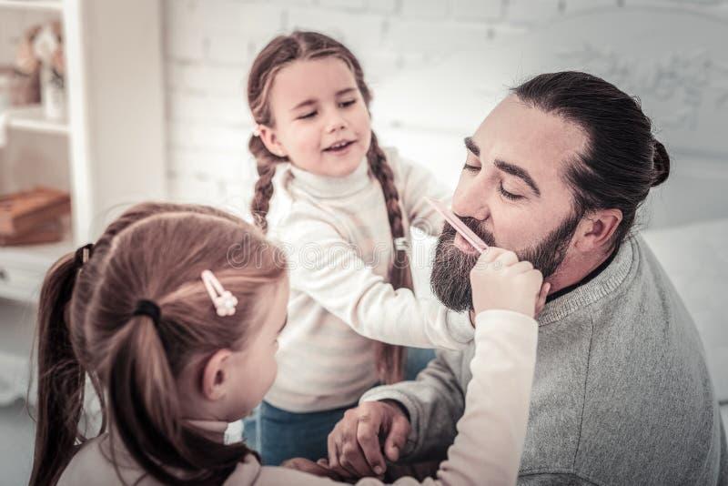 Fuoco sul padre che fa la sua comed barba dai suoi bambini svegli immagine stock libera da diritti