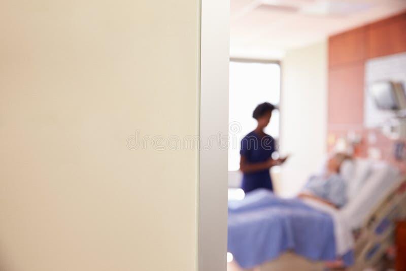 Fuoco sul segno della stanza di ospedale con l'infermiere Talking To Patient fotografia stock libera da diritti