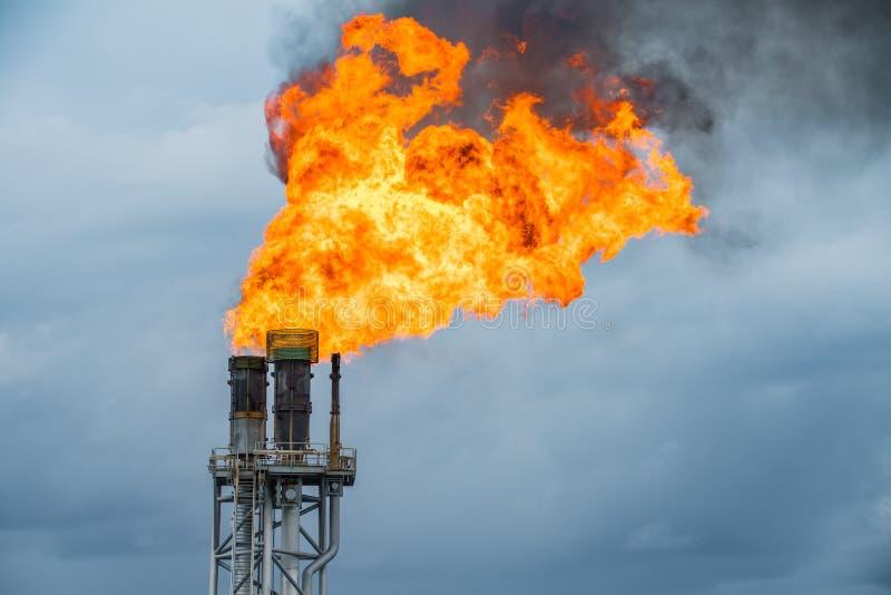 Fuoco sulla fiaccola alla piattaforma di elaborazione centrale del gas e del petrolio mentre bruciando sostanza tossica e rilasci immagine stock