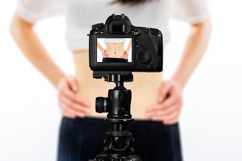 Fuoco sulla vista in tensione sulla macchina fotografica sul treppiede, adolescente con la scena vaga nel fondo Manifestazione li fotografie stock libere da diritti
