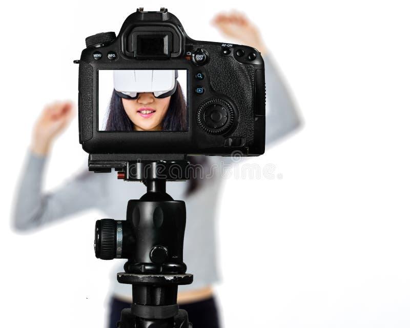 Fuoco sulla vista in tensione sulla macchina fotografica sul treppiede, adolescente con la scena vaga nel fondo Manifestazione li immagine stock libera da diritti