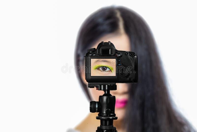 Fuoco sulla vista in tensione sulla macchina fotografica sul treppiede, adolescente con la scena vaga nel fondo Manifestazione li fotografia stock