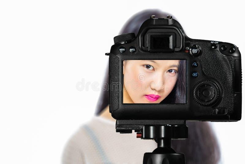 Fuoco sulla vista in tensione sulla macchina fotografica sul treppiede, adolescente con la scena vaga nel fondo Manifestazione li immagini stock