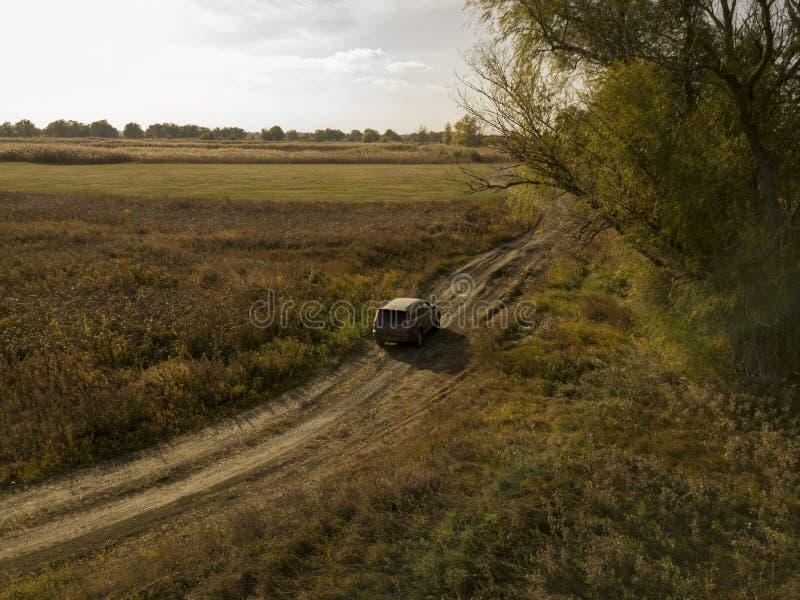 Fuori dall'automobile della strada sulla vista superiore f della strada non asfaltata di estate del campo e della foresta fotografia stock
