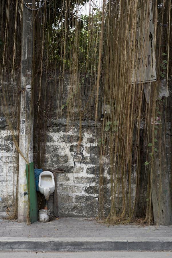 Fuori dell'orinale contro una parete di mattoni in una via di Manila, le Filippine immagini stock libere da diritti