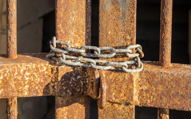 Fuori della vista di vecchia, catena arrugginita che cosa chiudono un vecchio, portone arrugginito del metallo di un'entrata del  fotografie stock