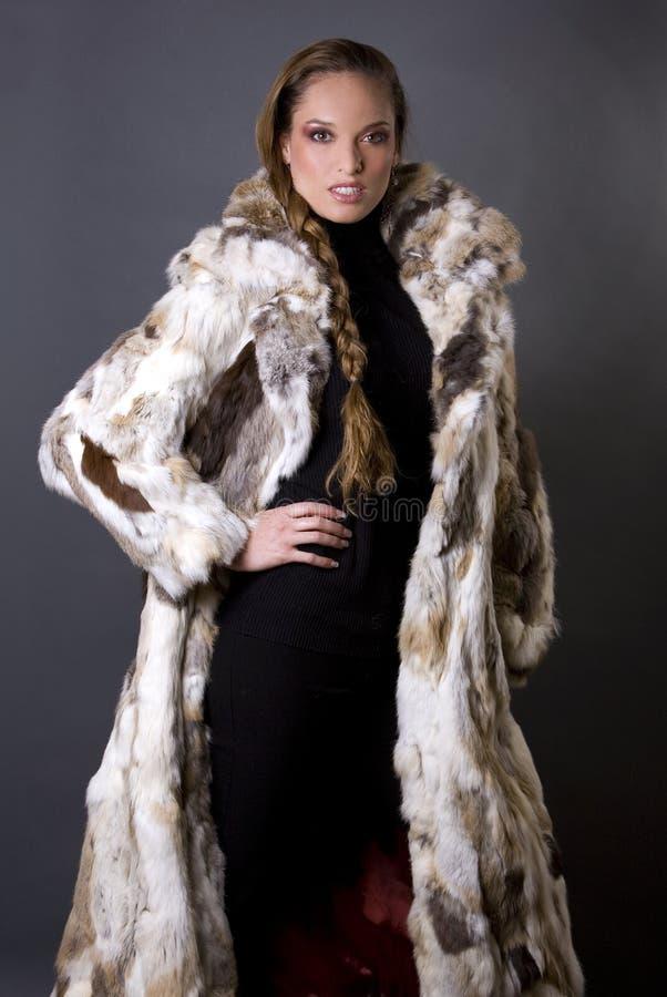 Fur coat. Pretty model wearing fur coat and black pants indoors royalty free stock photography