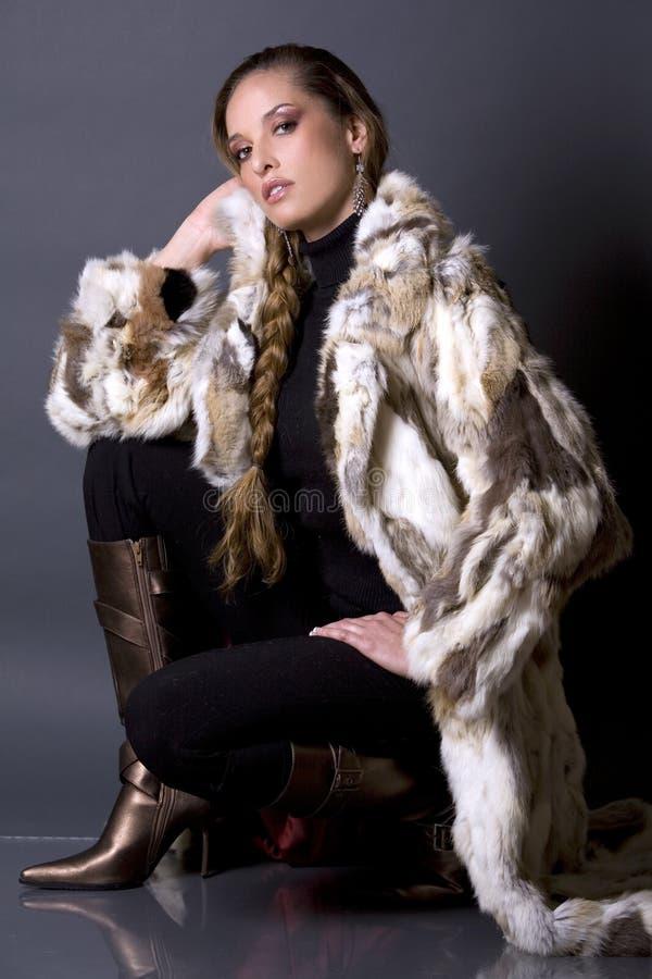 Fur coat. Pretty model wearing fur coat and black pants indoors royalty free stock photos