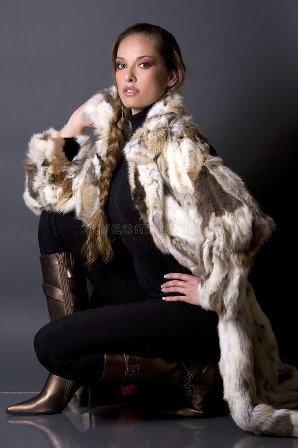 Fur coat. Pretty model wearing fur coat and black pants indoors royalty free stock images