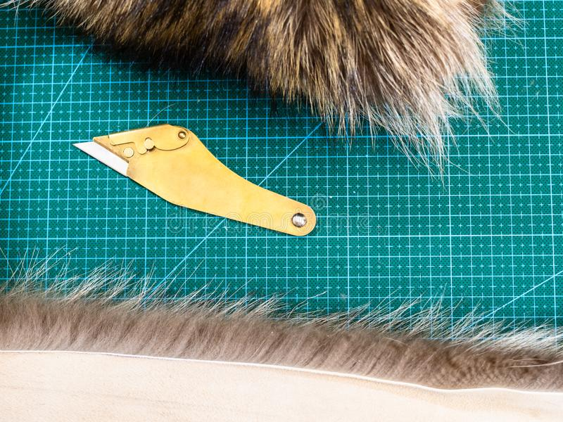 Fur knife between pieces of pelts on cutting mat. Workshop of manufacturing of coats from raccoon fur - fur knife between pieces of pelts on cutting mat royalty free stock photo