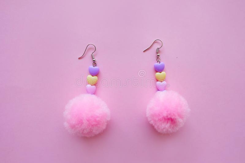 Fur Pink Round Earring Fashion Accessories. Beautiful Pink Pom Heart Earring Isolated on Pink Background. Great For Any Use stock photo