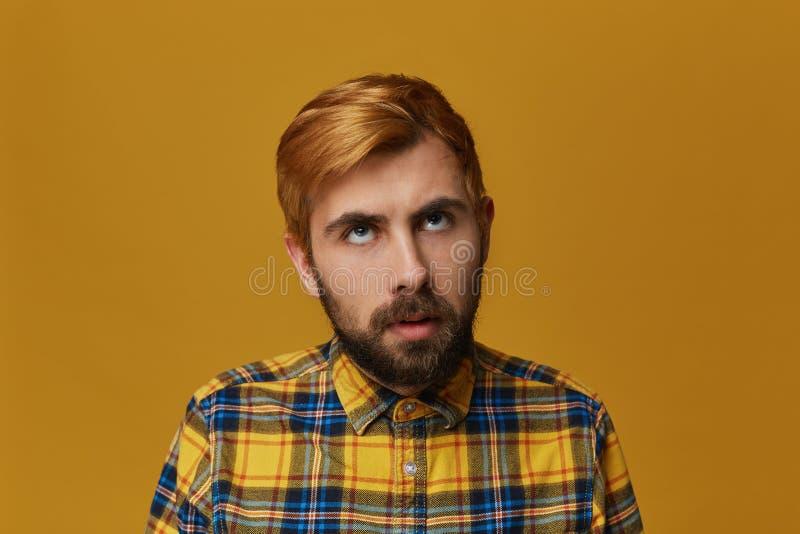 Furar à morte! O homem farpado novo, t-shirt amarelo vestindo, cabelo tingido sente furado e thinkin sobre a casa imagens de stock