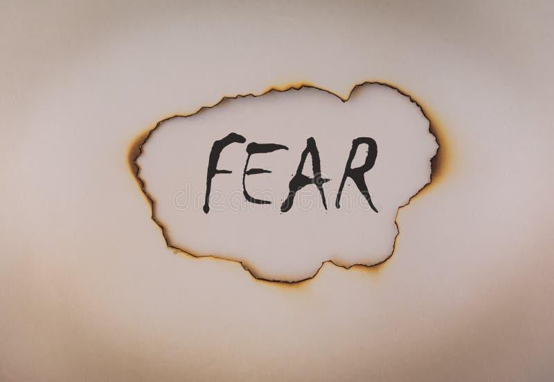 Furchtkonzept, Wort auf gebranntem Papier lizenzfreie stockfotos