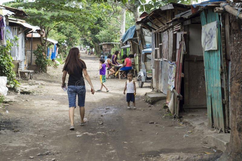 Furchtlose junge Dame, die entlang auf eine raue Straßenstraße des Elendsviertels unbegleitet geht lizenzfreie stockbilder