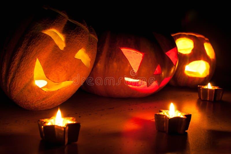 Furchtsame Halloween-Kürbis- und -melonensteckfassung-olaternen auf schwarzem Hintergrund beleuchteten mit kleinem um und Sternke stockbilder