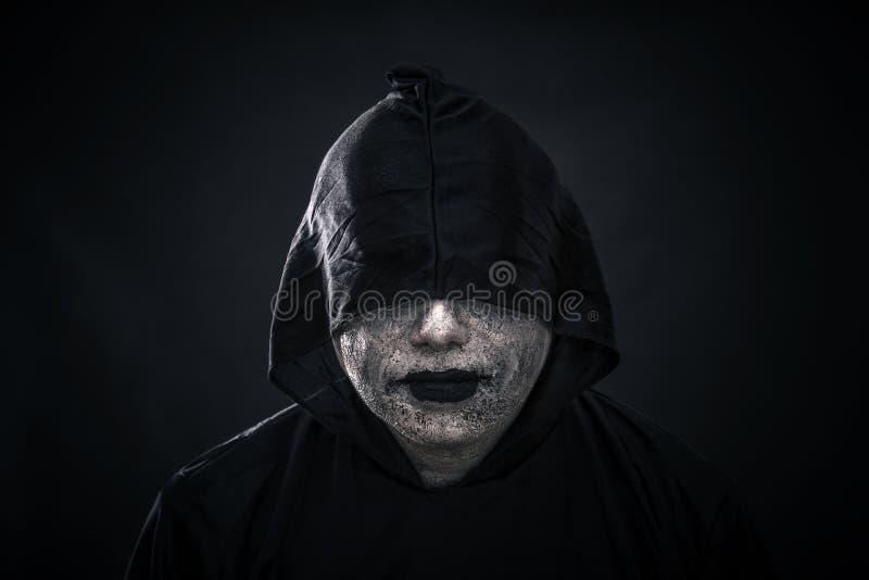 Furchtsame Zahl im mit Kapuze Mantel stockfoto