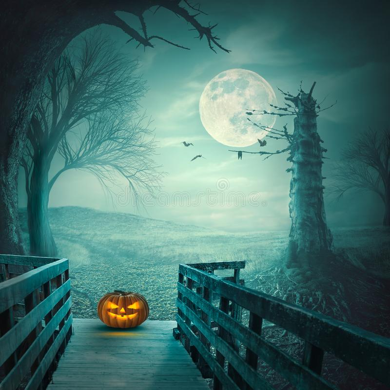 Furchtsamer Halloween-Kürbis auf Holzbrücke nachts Vollmond stockfotos