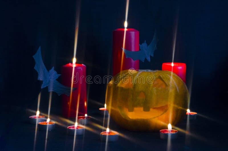 Furchtsamer Laternen-Halloween-Kürbis Jacks O mit brennendem Kerzenlichtinnere mit Schlägern stockfotografie