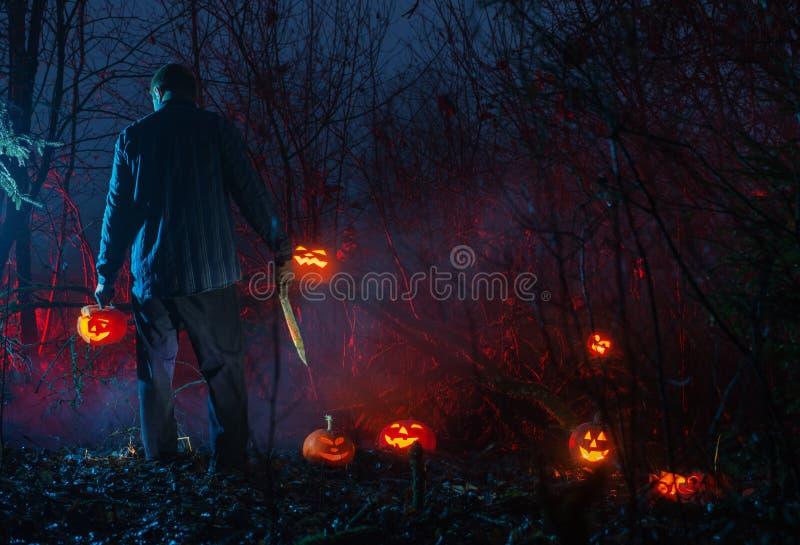 Furchtsamer Mann im Nachtwald schneidet Halloween-Kürbise stockbild