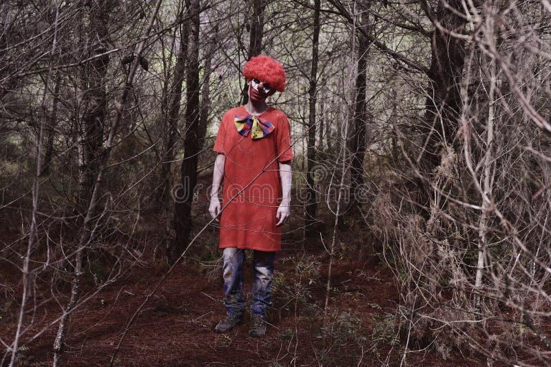 Furchtsamer schlechter Clown im Wald stockfotos