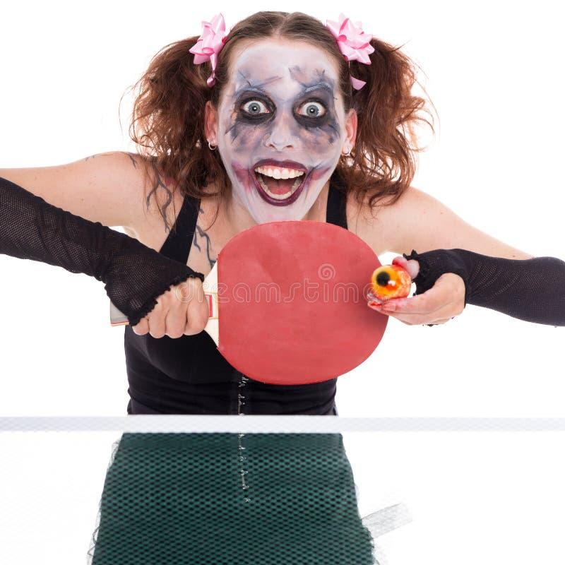 Furchtsamer weiblicher Clown spielt Tischtennis stockfoto