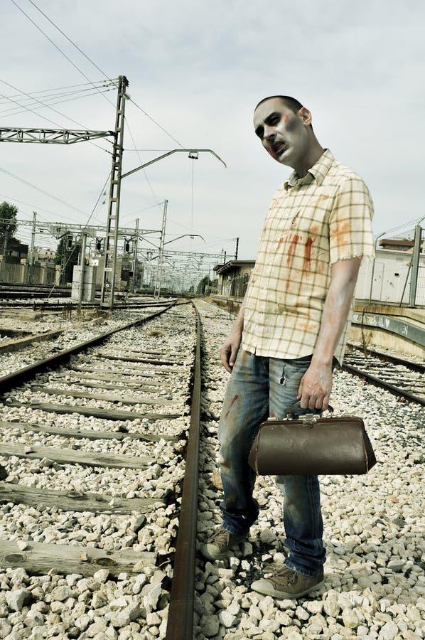 Furchtsamer Zombie, der auf den Zug, mit einem Filtereffekt wartet stockbild